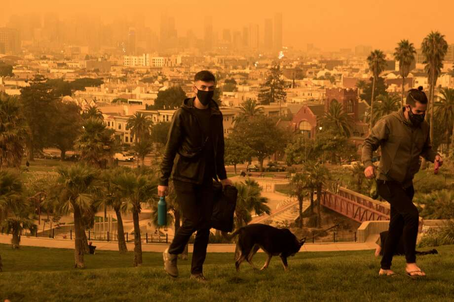 Two men walk up the hill at Dolores Park. Smoke from wildfires in California and Oregon spread over San Francisco on Sept. 9, 2020 darkening the skies to an orange hue. Photo: Douglas Zimmerman/SFGATE / SFGATE