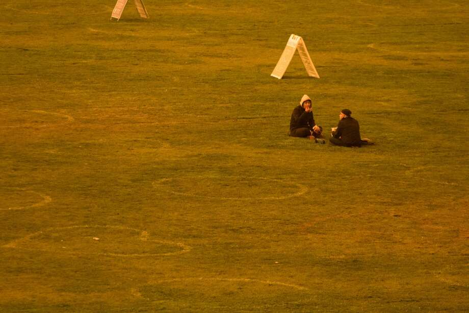 Two friends hang out in socially distanced circles at Dolores Park. Smoke from wildfires in California and Oregon spread over San Francisco on Sept. 9, 2020 darkening the skies to an orange hue. Photo: Douglas Zimmerman/SFGATE / SFGATE