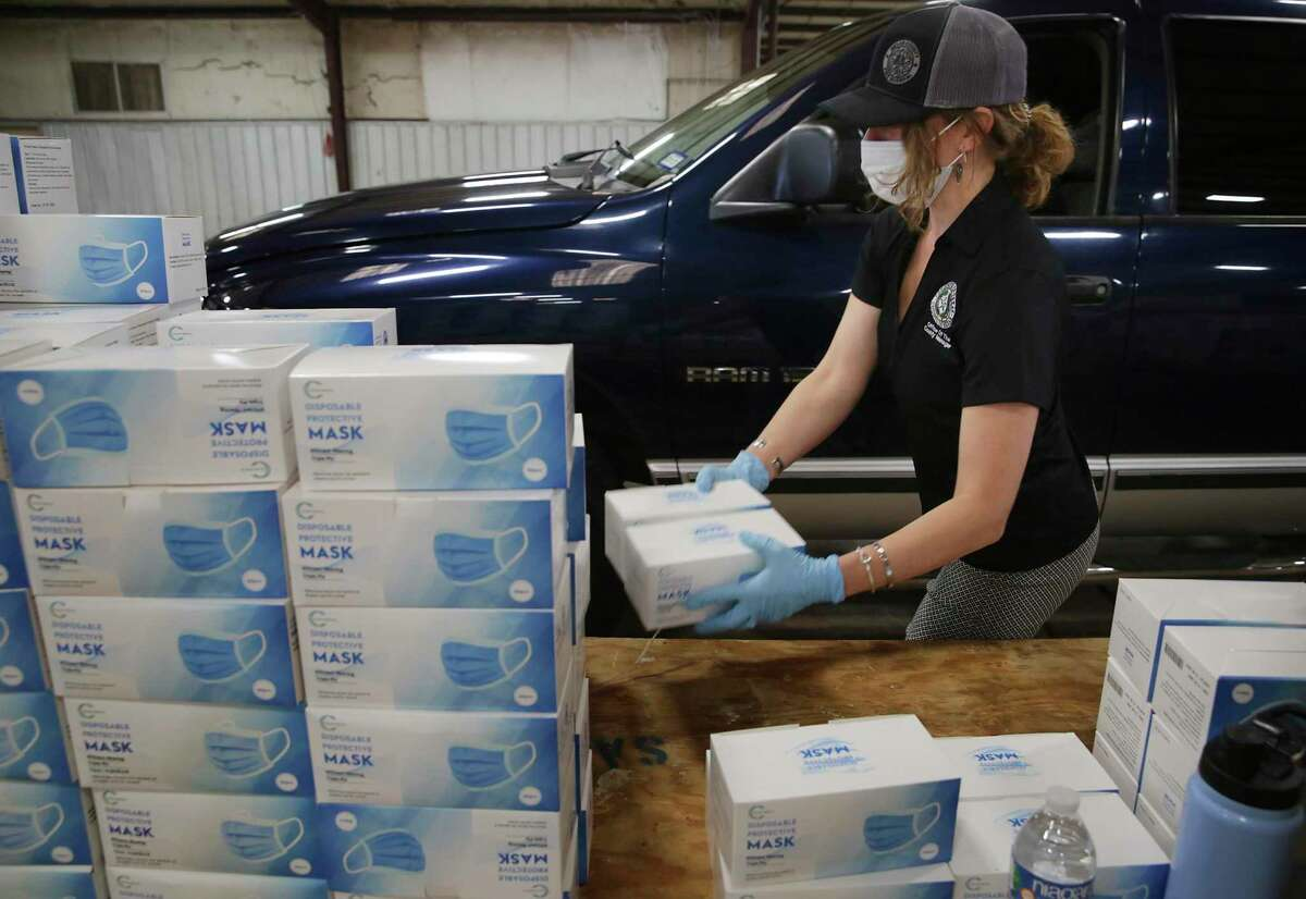 Cate Gruenburg, a worker in the Office of County Manager, hands out boxes of masks to Bexar County business owners June 24 at Freeman Coliseum. County commissioners will hold a second work session Thursday on a pandemic-era budget for 2021, and are expected to approve a final version Tuesday.