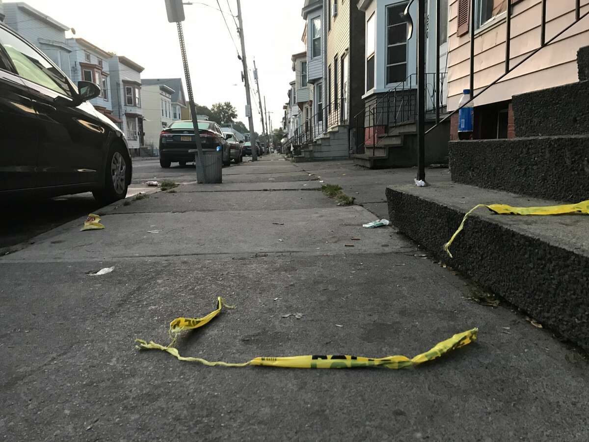 Remnants of police tape remain on the ground near where a 39-year-old man was shot and killed early Thursday on First Street. The killing, which occurred on the block between Quail and Ontario streets, is Albany's 14th homicide of the year.