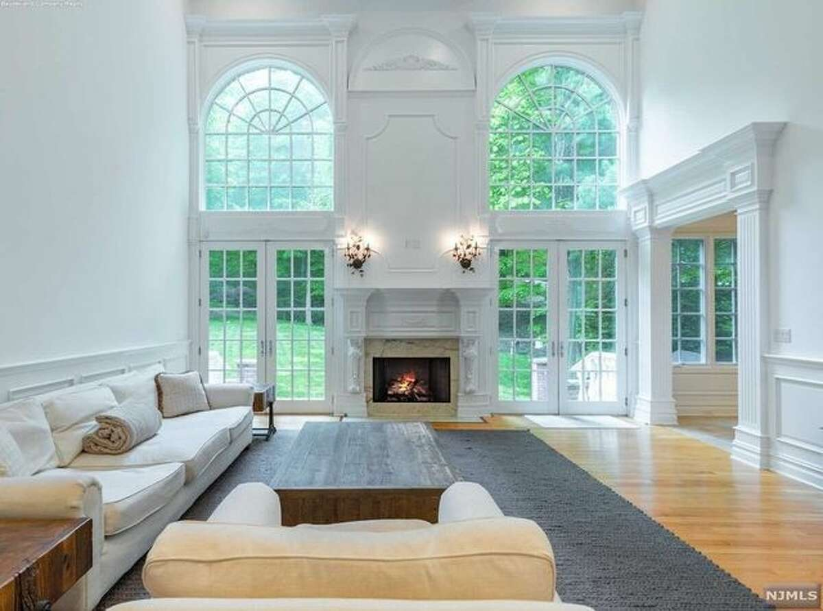 The impressive two-story foyer leads into a layout with architectural woodwork, expansive windows, and a total of six fireplaces, according to the listing details. The floor plan features a great room with vaulted ceilings and a wet bar, as well as a formal living room and a dining room with custom built-ins.