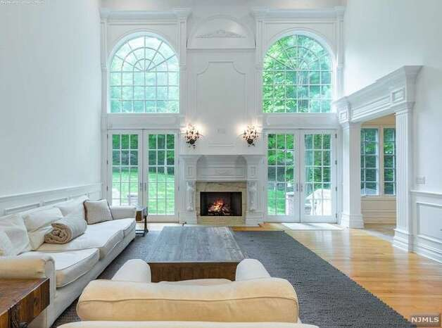 The impressive two-story foyer leads into a layout with architectural woodwork, expansive windows, and a total of six fireplaces, according to the listing details. The floor plan features a great room with vaulted ceilings and a wet bar, as well as a formal living room and a dining room with custom built-ins. Photo: Realtor.com