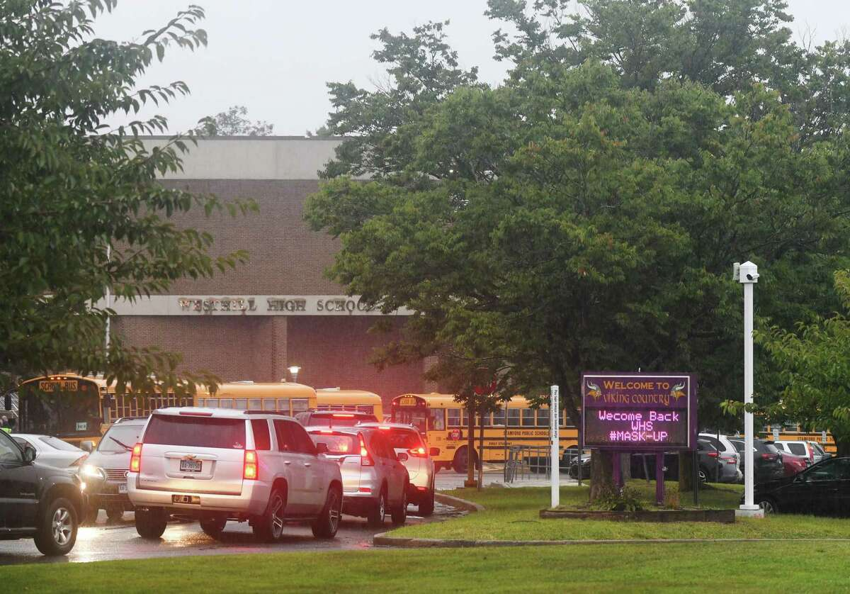 A sign reminds students to wear their masks as they return for the first day of the 2020-2021 school year at Westhill High School in Stamford, Conn. Thursday, Sept. 10, 2020. Westhill High School opened two days later than the other Stamford public schools. Teachers at the school bombarded administration with emails late last week saying the school was not ready to open due to issues concerning cleanliness, safety, and teachers not having clear assignments.