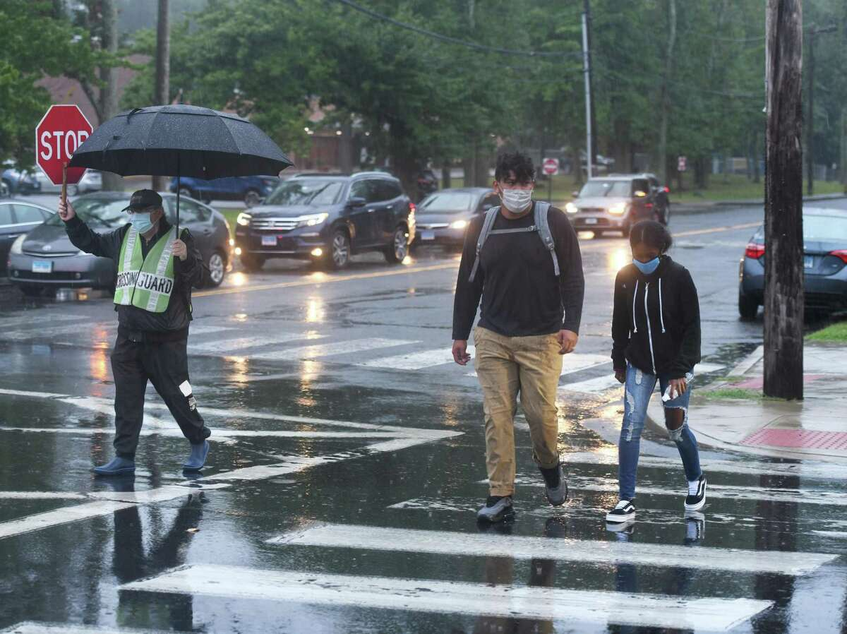 Junior Carlos Escobar and freshman Delilah Starrbagoulehi cross the street to return for the first day of the 2020-2021 school year at Westhill High School in Stamford, Conn. Thursday, Sept. 10, 2020. Westhill High School opened two days later than the other Stamford public schools. Teachers at the school bombarded administration with emails late last week saying the school was not ready to open due to issues concerning cleanliness, safety, and teachers not having clear assignments.
