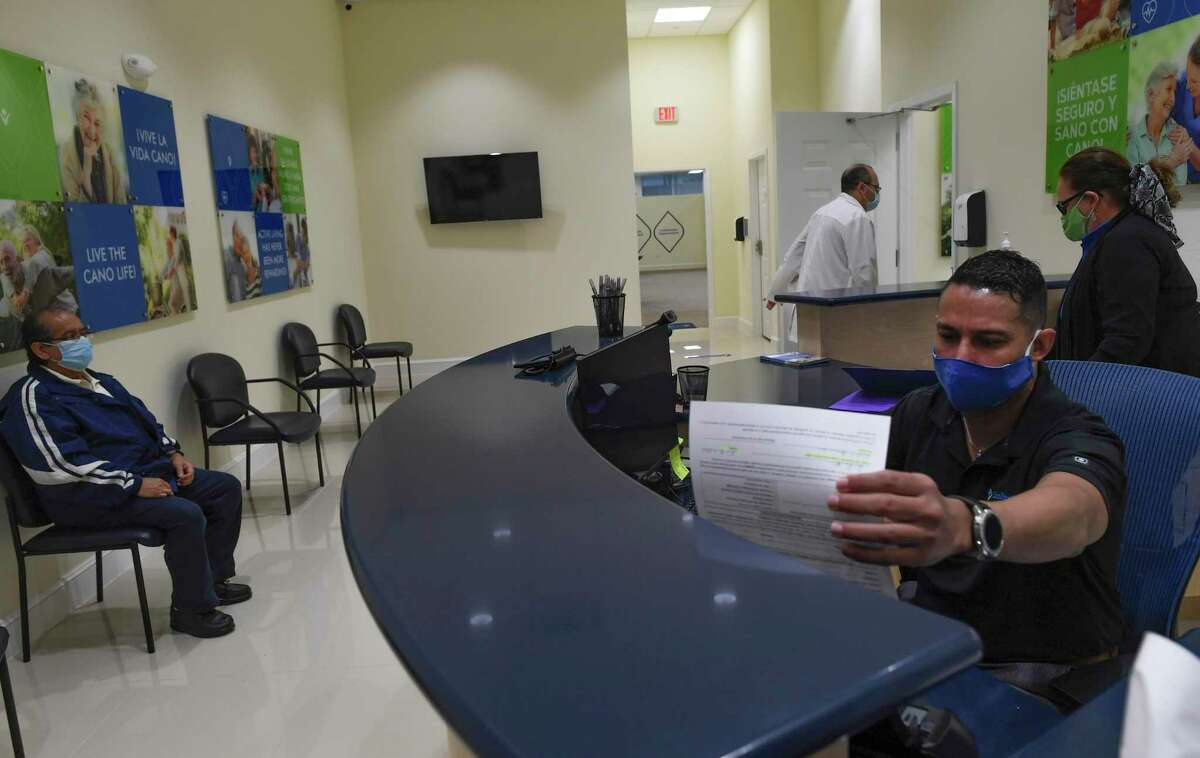 Front desk coordinator George Ruiz checks on paper work for patient Jose Hernandez, left, at the Cano Health location at 7031 Marbach Rd. on Tuesday, Sept. 8, 2020.