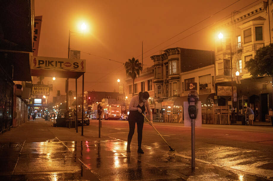 An employee washes the street in front of their store in the Mission District under cloudy orange sky. Heave smoke blotted out sunlight and turned day into night on Sept. 9, 2020. Photo: Anna Kariel
