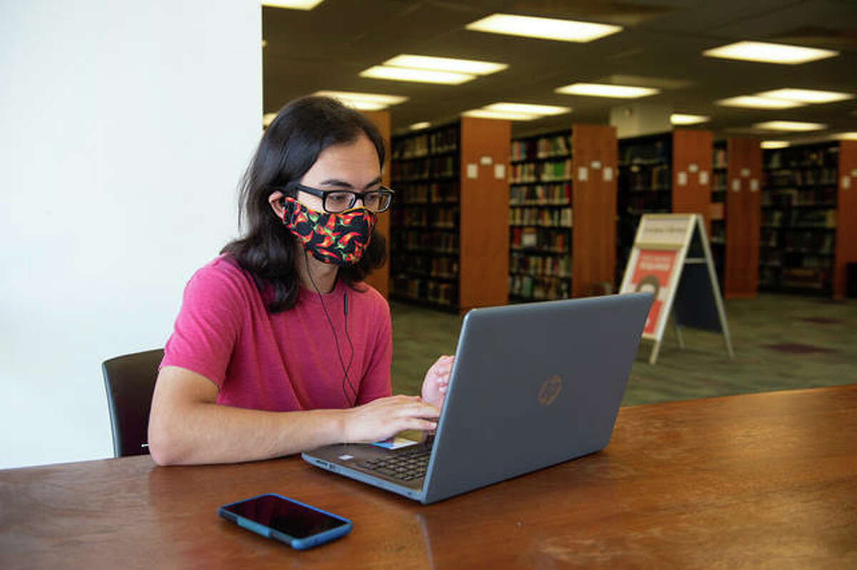 File photo: Saahil Regmi studies in the Lovejoy Library while wearing a mask.