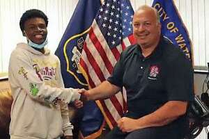 Waterbury Police Chief Fernando Spagnolo thanks Justin Gavin, 18, for saving the mother and her three children from a burning car on Wednesday, Sept., 2020.