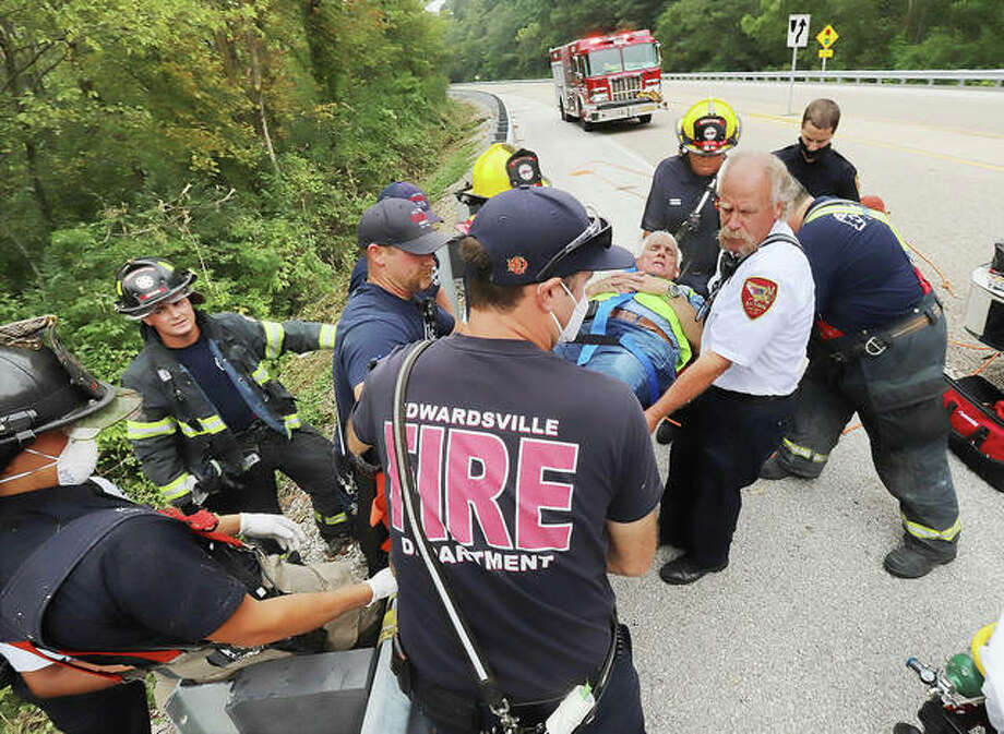 Alton firefighters, with help from Edwardsville firefighters who were in the area, lift an Illinois-American Water Company employee over the guardrail on the west side of MLK Boulevard south of 20th Street in Alton Thursday morning after a difficult rescue. The worker, who was apparently standing on top of a large box culvert on the east side of the roadway, slipped and fell into a wooded area below, with trees making it impossible for firefighters to retrieve him. So firefighters carried him through the box culvert to the west side where a path was cleared and the man was remove for transport to a hospital for his non-life threatening injuries.