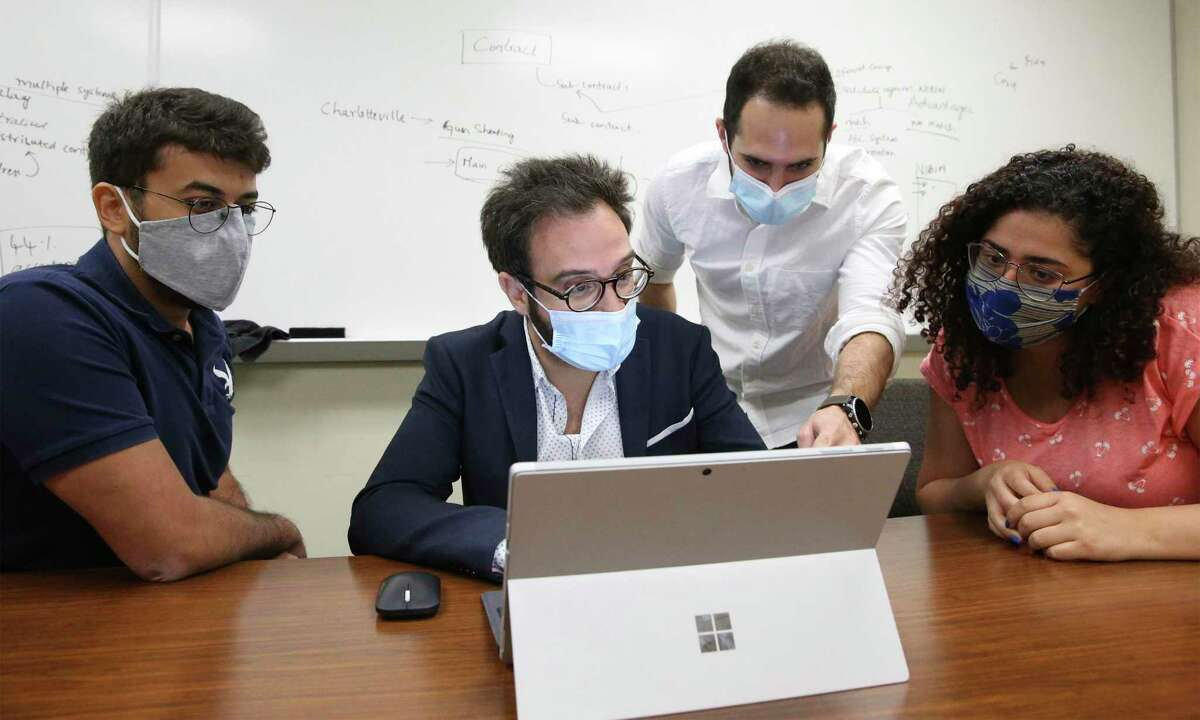 Elias Bou-Harb works with his staff last week researching the increased hacking of smart devices during the coronavirus pandemic. From left are Joseph Khoury, a doctoral student, Bou-Harb, Morteza Safaei Pour, a doctoral student, and Christelle Nader, a masters student.