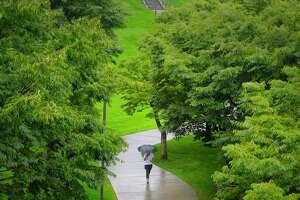 A woman walks along a path in the rain on Thursday, Sept. 10, 2020, in Albany, N.Y.   (Paul Buckowski/Times Union)