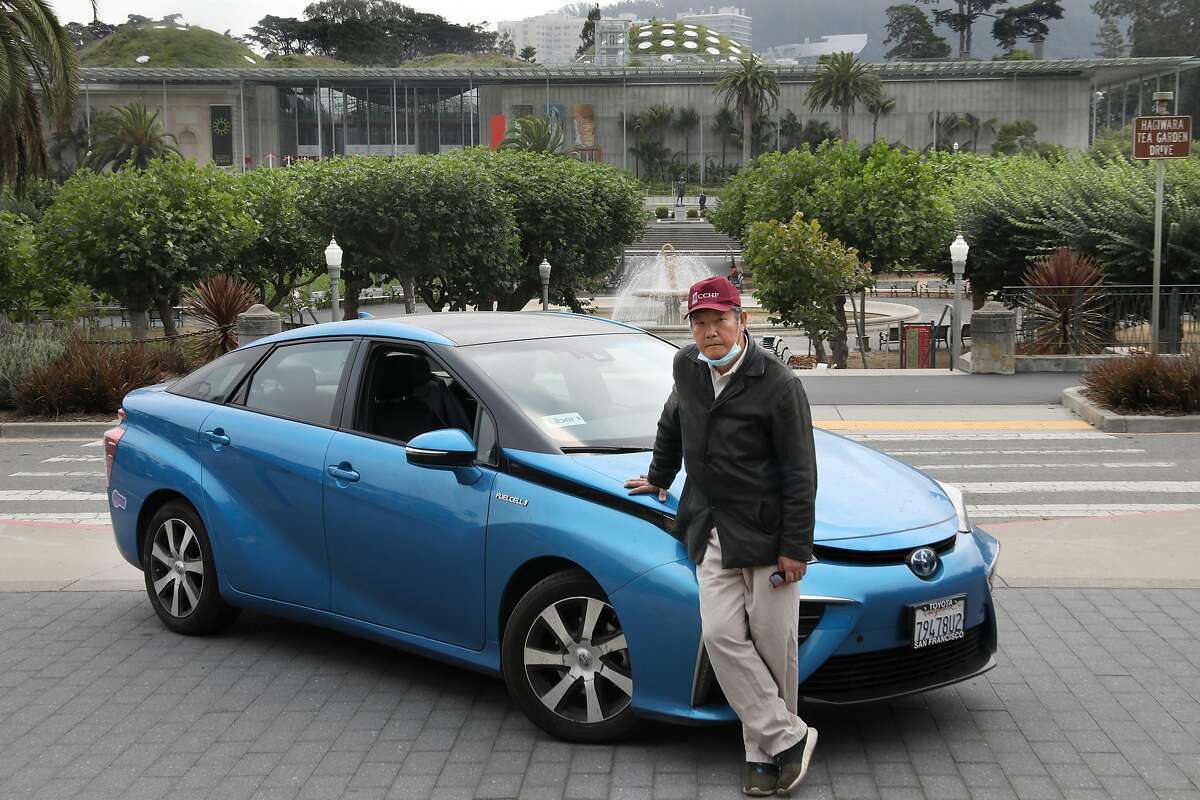 Jian Xiao, 64, was laid off from a job as a cook at the Calif. Academy of Sciences and also stopped his part-time Uber driving and is seen with his Uber car and the museum in the background at Golden Gate park on Tuesday, Sept. 1, 2020, in San Francisco, Calif. He misses Sundays when he could hear music coming from the bandshell.