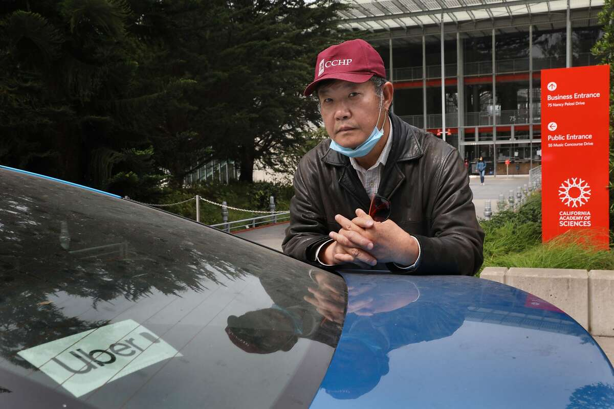 Jian Xiao, 64, was laid off from a job as a cook at the Calif. Academy of Sciences and also stopped his part-time Uber driving and is seen with his Uber car and the employee entrance to the museum in the background at Golden Gate park on Tuesday, Sept. 1, 2020, in San Francisco, Calif.