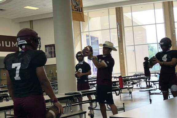 First-year Northbrook High School football head coach Andres Gomez demonstrates techniques to the wide receivers during practice on Sept. 9, which was held inside due to lightning in the area. Gomez was a wide receiver on the 1997 Katy High School state championship football team.