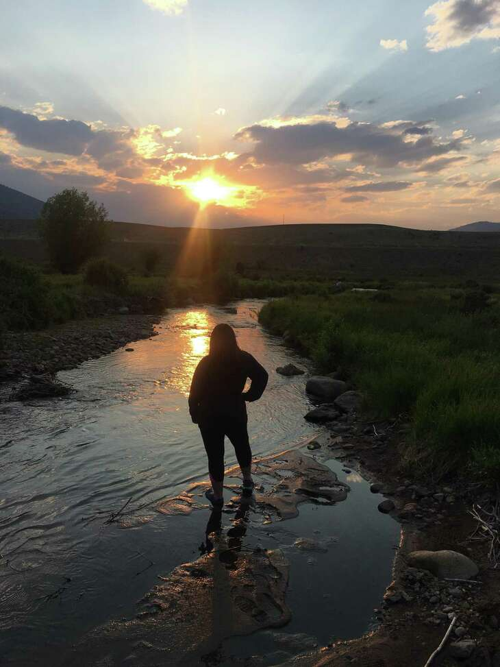 Tessa Aguilar watches the sunset near Creede, Colo.