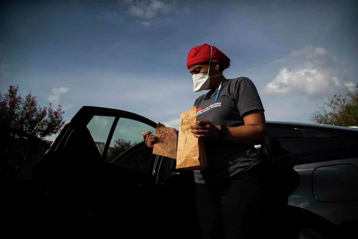 Kira Smith of the group Doctors Without Borders holds paper bags containing N95 masks on Wednesday, Sept. 9, 2020, in Jersey Village before entering a nursing home.