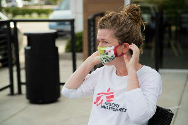 Rebecca Ricards of the nonprofit Doctors Without Borders puts on a cloth protective mask at a morning meeting with colleagues Wednesday, Sept. 9, 2020, in Houston.