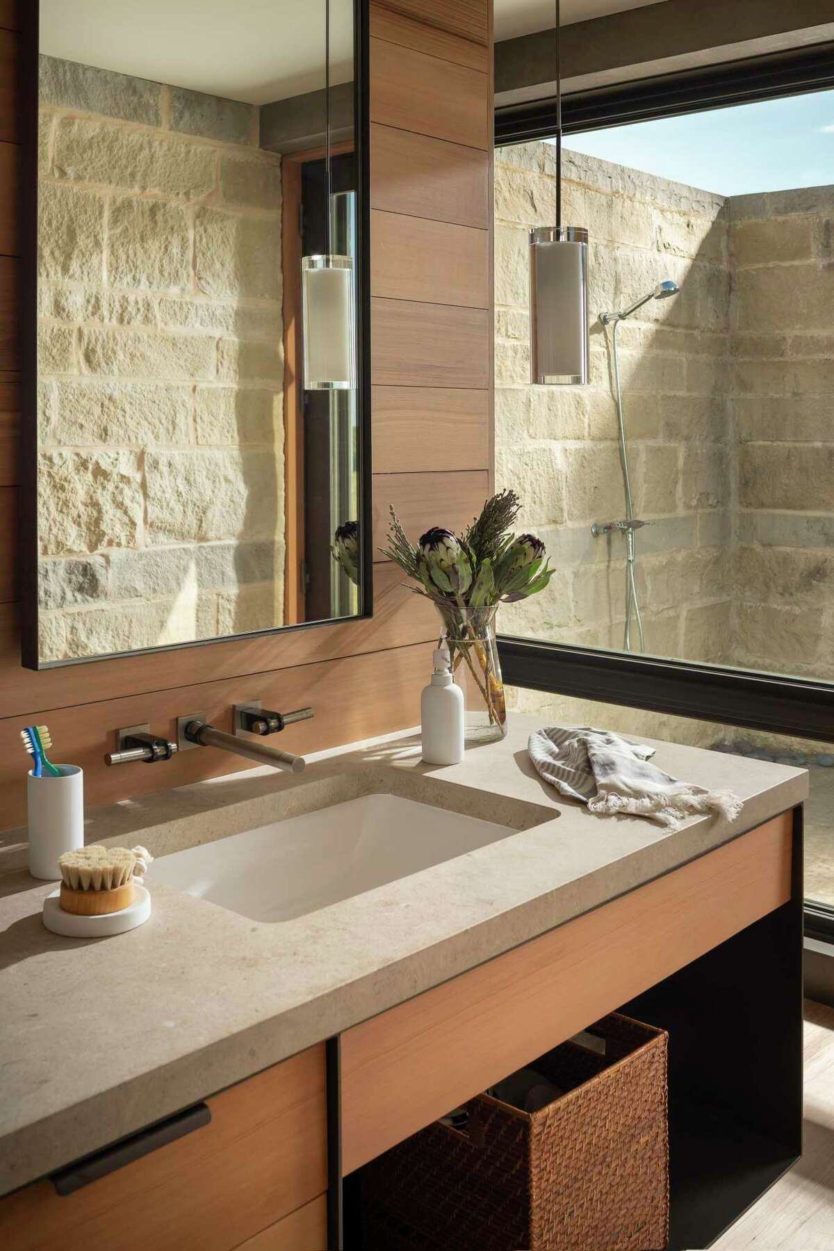A limestone outdoor shower sits just outside the master bathroom.