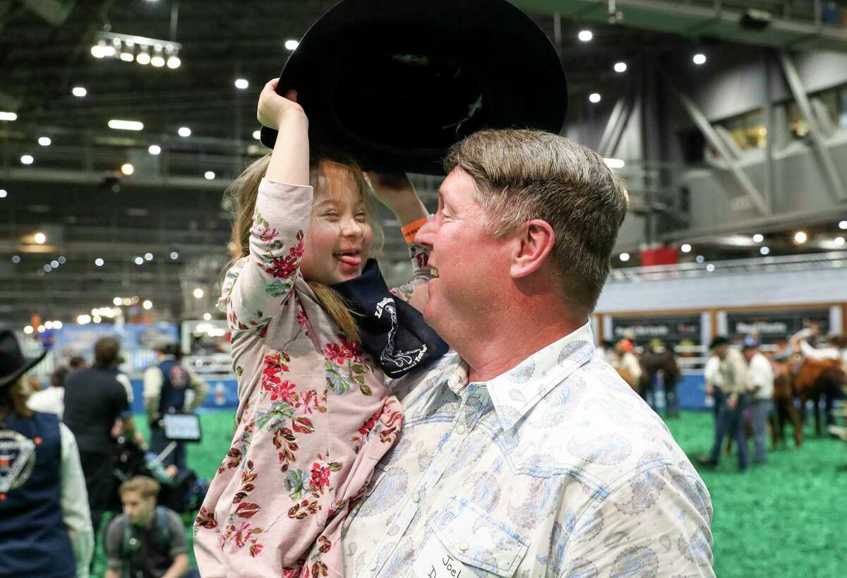 """Avery Hartman, 6, grabs the hat off volunteer Joel Dawson's head as they participate in the Lil' Rustler's Rodeo at the Houston Livestock Show and Rodeo on Tuesday, March 10, 2020, at NRG Stadium in Houston. Hartman's mother said Avery is diagnosed with Down Syndrome. """"We're excited to have her included in this event, because we're trying to bridge the gap between society and children with special needs,"""" said Avery's mom, Sarah Hartman."""