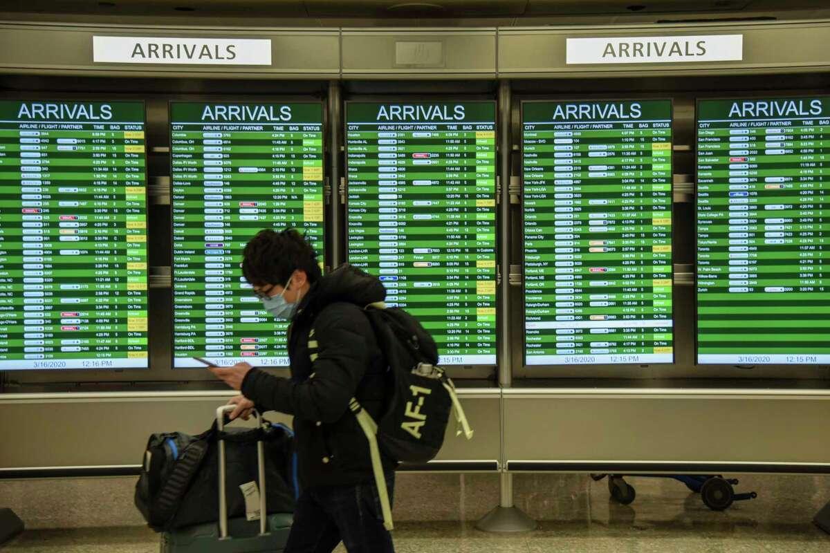 Travelers pass through Dulles International Airport.