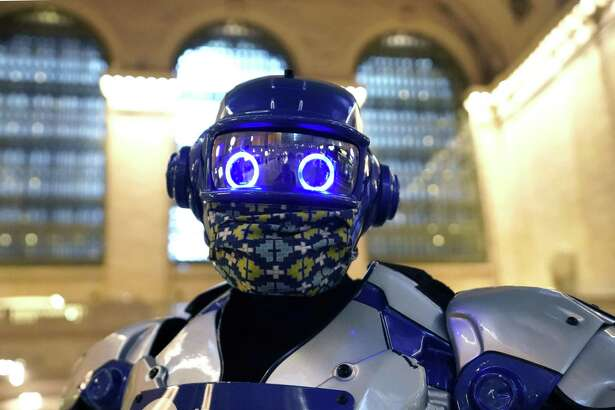 MTA-North Railroad's mascot, Metro-Man hands out face mask to commuters as they arrive at Grand Central Terminal on September 2, 2020 in New York. - Facemasks are required to ride the MTA's Metro-North Railroad, which serves New York and parts of New York state and Connecticut, as the face coverings are a critical tool in the fight against covid-19. On Monday, Sept. 14, 2020, a new $50 fine will be imposed on people without a mask.