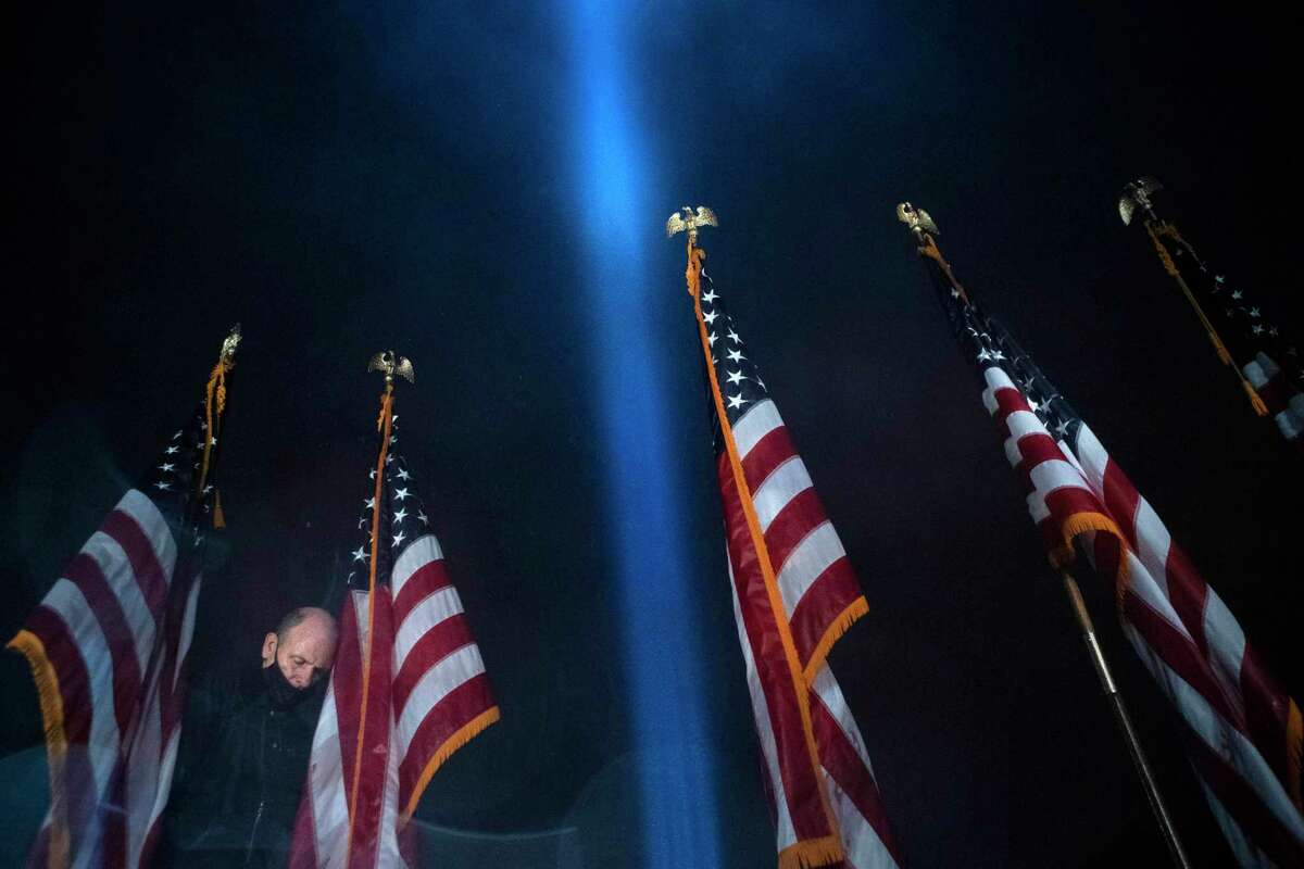A worker removes the American flags after the ceremony as a beam of light is seen over the Pentagon, as part of the Towers of Light Tribute marking the 19th anniversary of the 9/11 attack on the Pentagon, Sept. 9, in Washington.