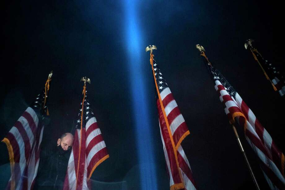 A worker removes the American flags after the ceremony as a beam of light is seen over the Pentagon, as part of the Towers of Light Tribute marking the 19th anniversary of the 9/11 attack on the Pentagon, Sept. 9, in Washington. Photo: Jose Luis Magana / Associated Press / Copyright 2020 The Associated Press. All rights reserved