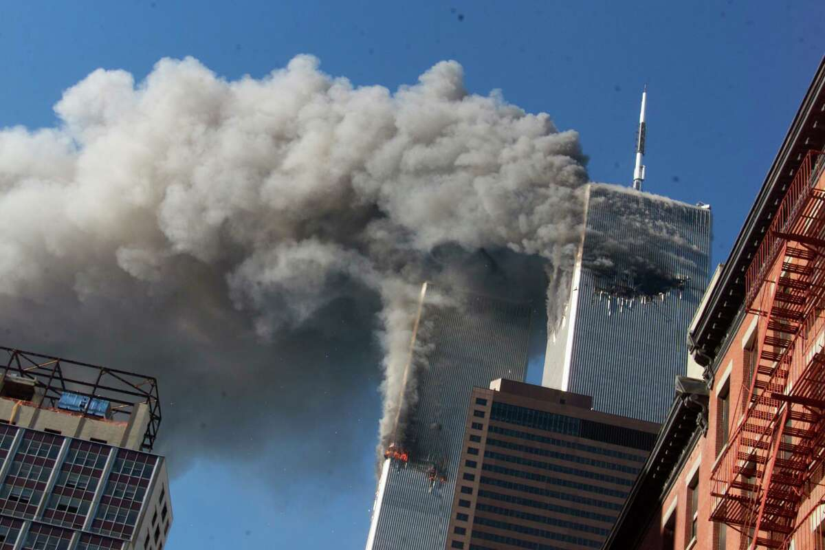 Smoke rises from the burning twin towers of the World Trade Center after hijacked planes crashed into the towers, in New York City on Sept. 11, 2001. The coronavirus pandemic has reshaped how the U.S. is observing the anniversary of 9/11.