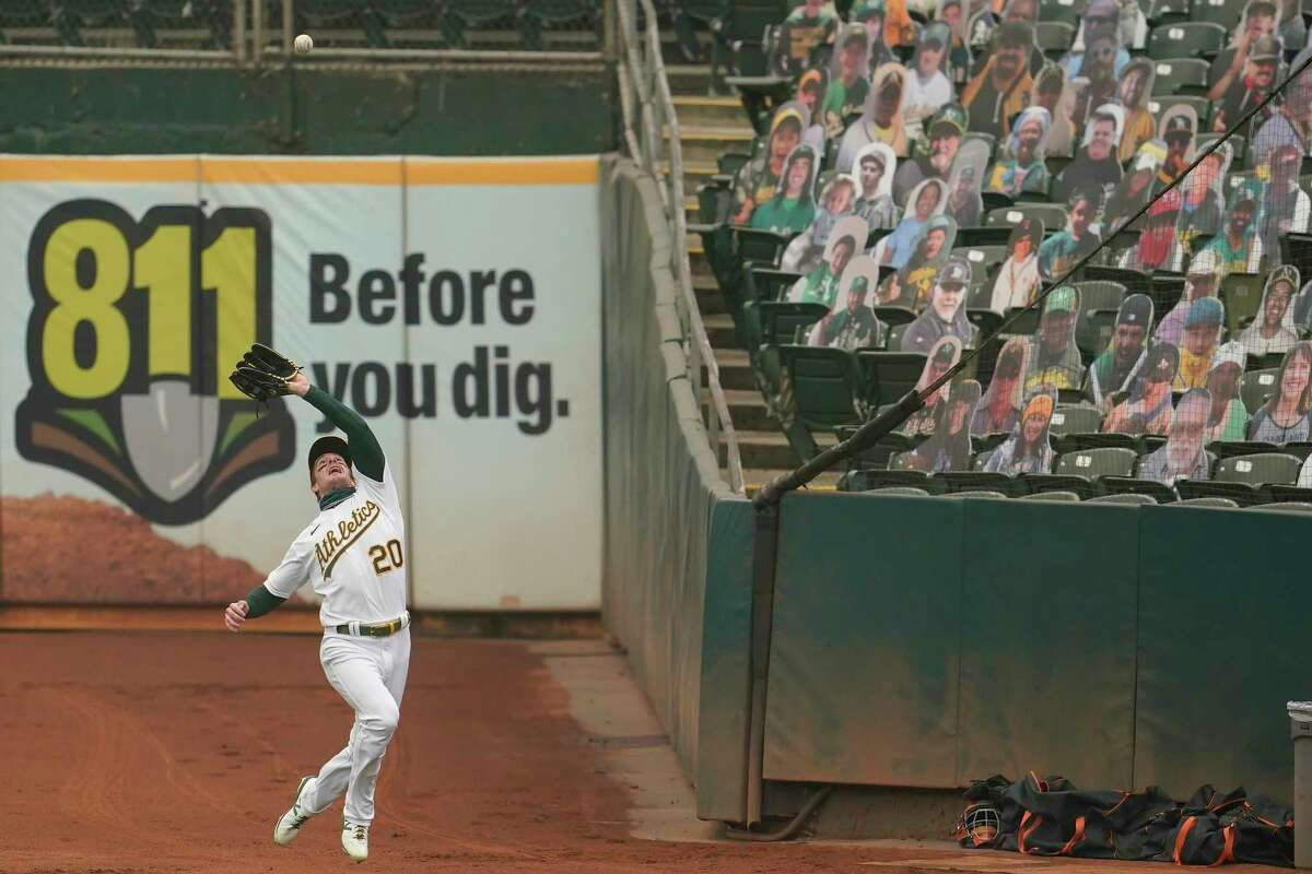 Oakland Athletics right fielder Mark Canha (20) makes the catch on Houston Astros' Alex Bregman's foul fly ball during the first inning of a baseball game in Oakland, Calif., Thursday, Sept. 10, 2020. (AP Photo/Jeff Chiu)
