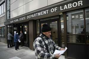 FILE - In this March 18, 2020 file photo, visitors to the Department of Labor are turned away at the door by personnel due to closures over coronavirus concerns in New York. A record-high number of people applied for unemployment benefits last week as layoffs engulfed the United States in the face of a near-total economic shutdown caused by the coronavirus. The surge in weekly applications for benefits far exceeded the previous record set in 1982. (AP Photo/John Minchillo, File)