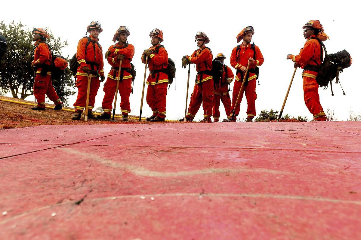 Inmate firefighters prepare to take on the River Fire in Salinas, Calif., Monday, Aug. 17, 2020. Fire crews across the region scrambled to contain dozens of blazes sparked by lightning strikes as a statewide heat wave continues. (AP Photo/Noah Berger)