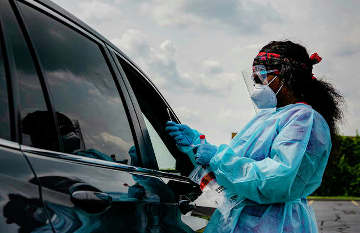 Phlebotomist Kainna Berry finishes testing a patient for COVID-19 at the drive-thru testing site at the Gateway Convention Center in Collinsville hosted by the Madison County Health Department on Tuesday.