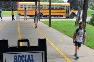 Spectrum/New Milford Public Schools opened Sept. 8, 2020 under the hybrid model. In days leading up to the opening, families from several of the town's schools picked up Chrome Books and school supplies at Sarah Noble Intermediate School. Above, John MacDonald, a second grader, follows the marked sidewalk for his first day at Northville Elementary School.