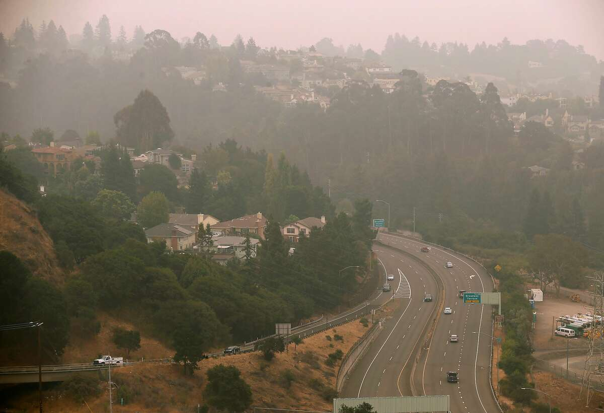 Traffic rolls through smoky conditions on Highway 13 in Oakland, Calif. on Thursday, Sept. 10, 2020. The orange hue is gone but smoke from wildfires burning in Northern California and the Pacific Northwest continue to foul the air quality in the region.