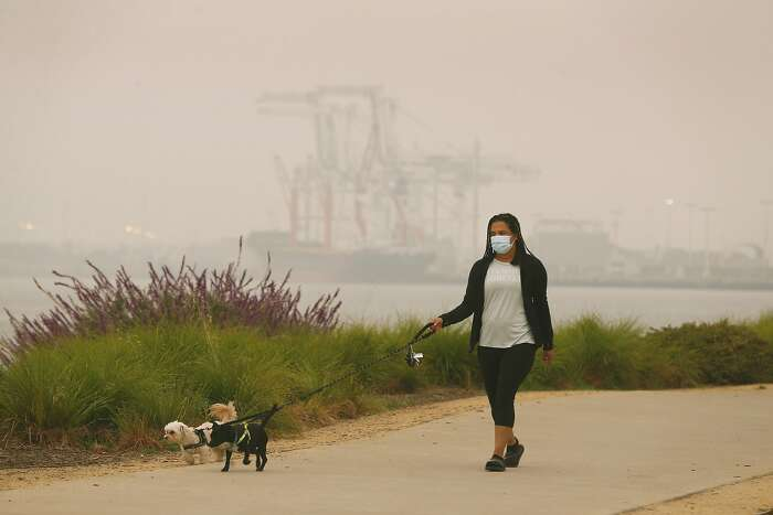 Reyna Parenteau walks dogs Sadie and Beejee despite the smoky conditions near Jack London Square in Oakland, Calif. on Thursday, Sept. 10, 2020. The orange hue is gone but smoke from wildfires burning in Northern California and the Pacific Northwest continue to foul the air quality in the region.