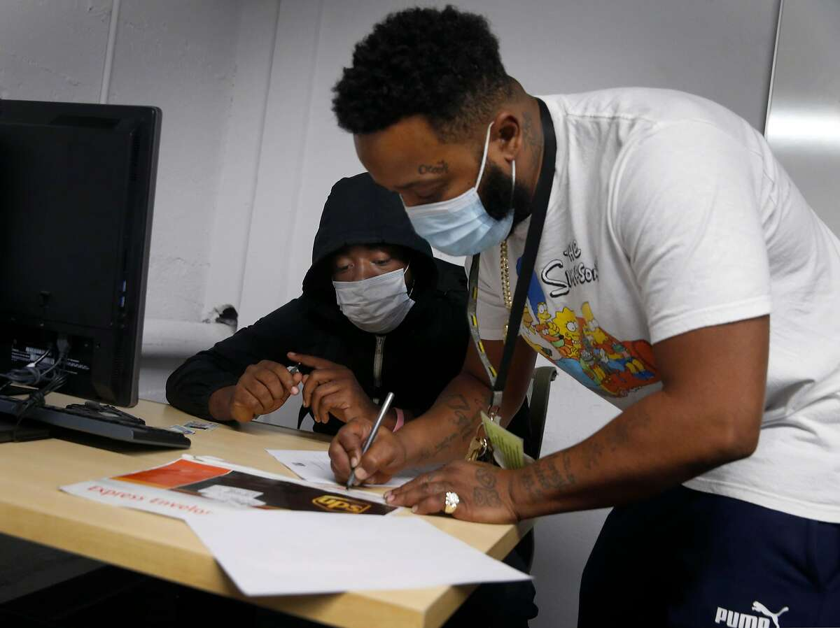 Jamal Gerry (left) receives assistance from Michael Jefferson in an employment training program at Larkin Street Youth Services in the Tenderloin in San Francisco, Calif. on Wednesday, Sept. 9, 2020. The center's future could be in doubt if a number of measures on the November ballot are rejected by voters.