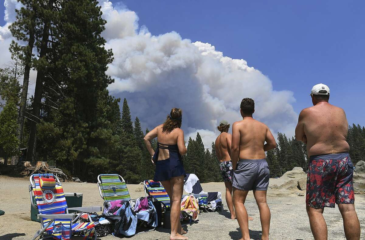 A family from Ventura County watches, from the shore of Shaver Lake, the billowing smoke from the Creek Fire, Saturday, Sept. 5, 2020, northeast of Fresno, Calif. (Eric Paul Zamora/The Fresno Bee via AP)
