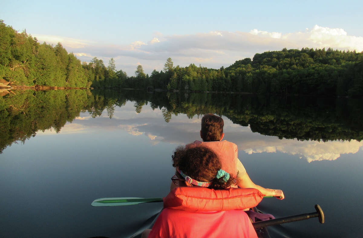 Gillian Scott and her daughter enjoy an evening paddle on Newcomb Lake (Herb Terns / Times Union)