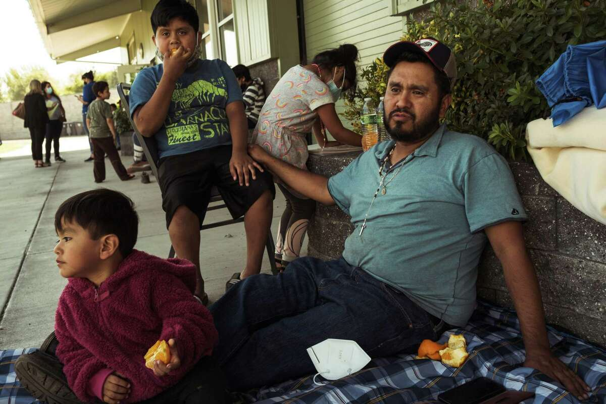 Jario Gomez and his children Adriel Gomez, 2 left, Adam Gomez, 10, and Aileen Gomez, 5, hang out under the shade at an evacuation center in Medford, Ore., on Wednesday, Sept. 9, 2020.