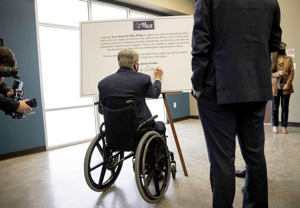 """Texas Gov. Greg Abbott signs a """"Texas Backs the Blue Pledge"""" on Thursday Sept. 10, 2020."""