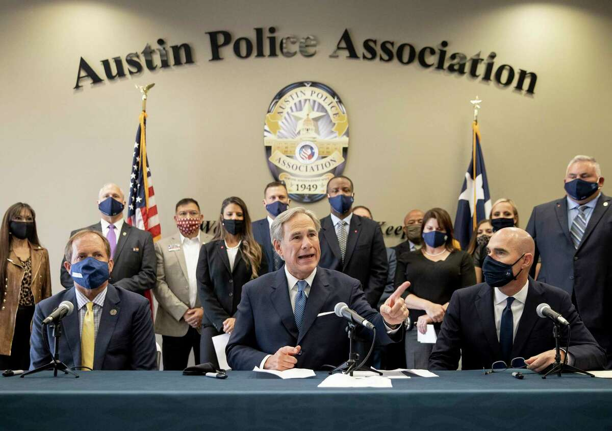 """Gov. Greg Abbott speaks at a news conference with Texas Attorney General Ken Paxton, left, and Speaker Dennis Bonnen before signing a """"Texas Backs the Blue Pledge"""" on Thursday Sept. 10, 2020, in Austin."""
