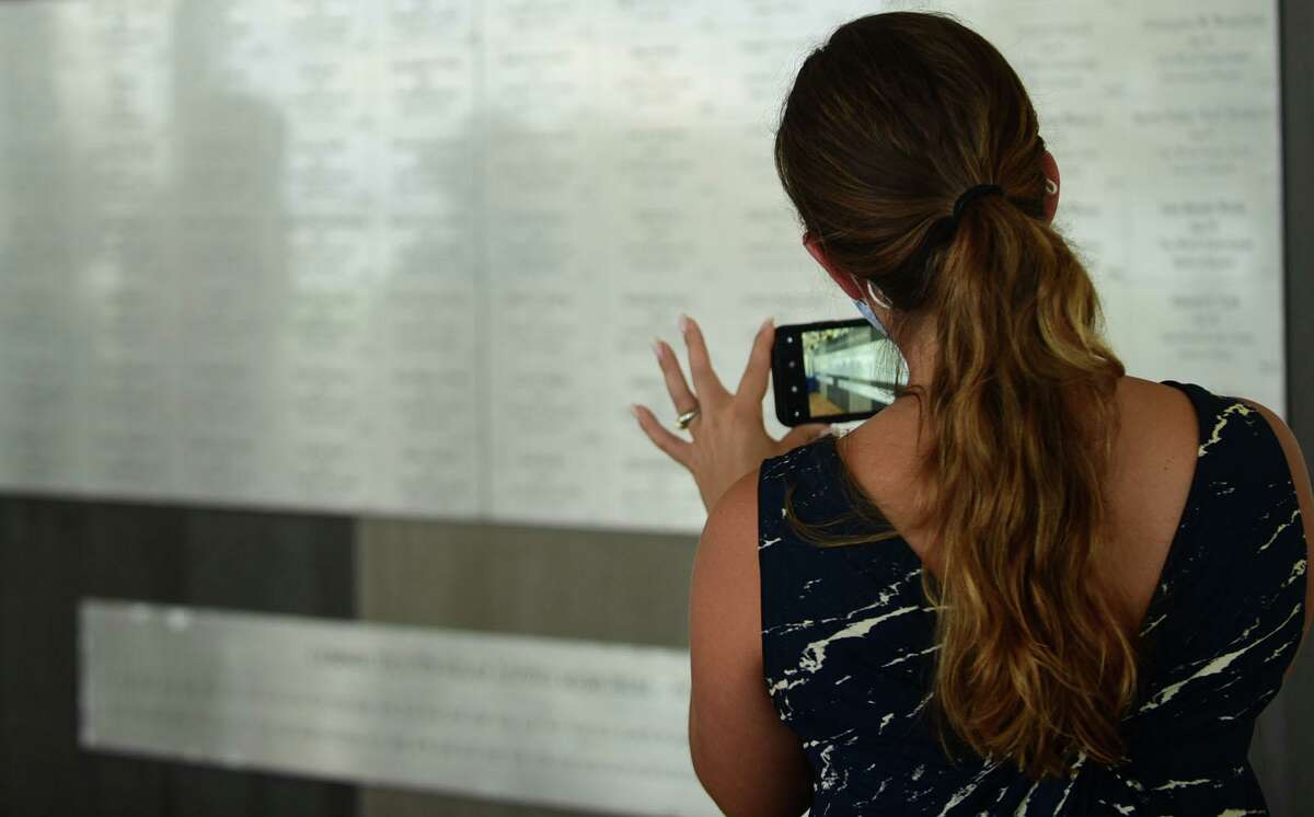Visitors take photos of the indoor memorial as Connecticut holds the 19th annual 9/11 memorial ceremony Thursday, September 10th, 2020, at Sherwood Island State Park in Westport, Conn. The ceremony is held yearly to honor and celebrate the lives lost in the Sept. 11, 2001 terror attacks. Family members of those killed in the attacks participated in the ceremony, and the names of the 162 victims with Connecticut ties were read aloud.
