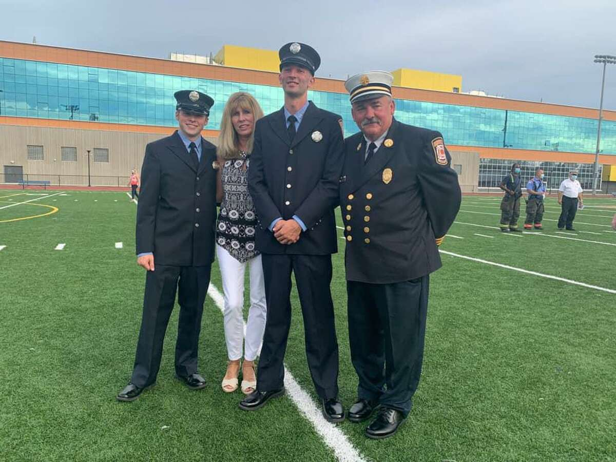 Austin (far left) and Ryan Hathaway became rookie Bridgeport firefighters during Wednesday's ceremony. Here they are pictured with their father, Assistant Fire Chief William Hathaway.