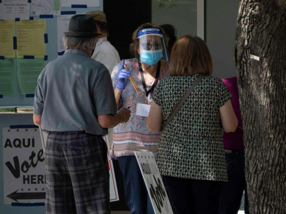 Citizens arrive to vote at Brook Hollow Library, 530 Heimer Road, as a poll worker, clad in protective gear against the coronavirus, offers them pencils on July 14, 2020. A federal appeals court Thursday upheld a state law that only voters older than 65 may receive a mail-in ballot without providing a reason.