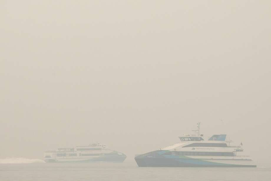 Two ferries pass on San Francisco Bay under smoky skies on Sept. 10, 2020. Photo: Douglas Zimmerman / SFGATE