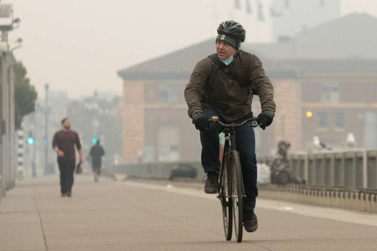 A bicyclist rides along the Embarcadero under smoky, grey skies on Sept. 10, 2020.