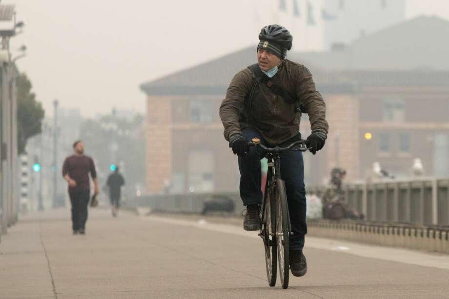 A bicyclist rides along the Embarcadero under smoky, grey skies on Sept. 10, 2020. Photo: Douglas Zimmerman / SFGATE