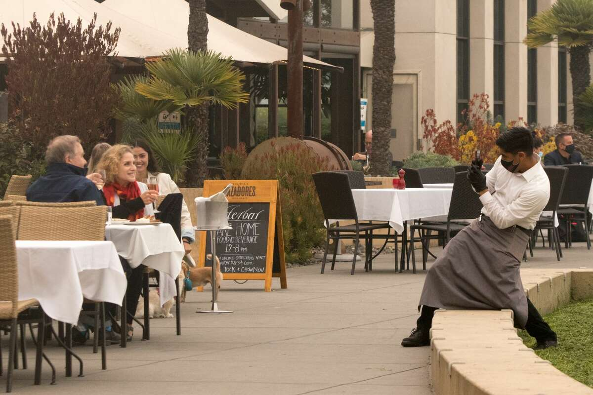 A waiter takes a photo of a couple at the Waterbar under smoky skies in San Francisco on Sept. 10, 2020.