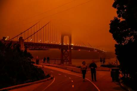 People check out the Golden Gate Bridge which was shrouded in dark orange smoke in San Francisco, Calif. Wednesday, September 9, 2020 due to multiple wildfires burning across California and Oregon.