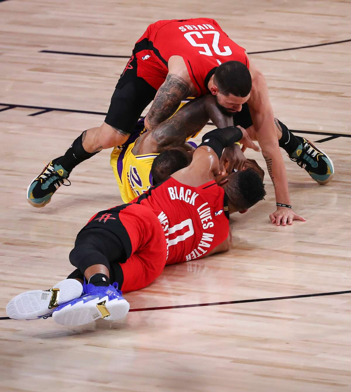 LAKE BUENA VISTA, FLORIDA - SEPTEMBER 10: LeBron James #23 of the Los Angeles Lakers scrambles for a loose ball against Russell Westbrook #0 of the Houston Rockets and Austin Rivers #25 of the Houston Rockets during the fourth quarter in Game Four of the Western Conference Second Round during the 2020 NBA Playoffs at AdventHealth Arena at the ESPN Wide World Of Sports Complex on September 10, 2020 in Lake Buena Vista, Florida. NOTE TO USER: User expressly acknowledges and agrees that, by downloading and or using this photograph, User is consenting to the terms and conditions of the Getty Images License Agreement. (Photo by Michael Reaves/Getty Images)